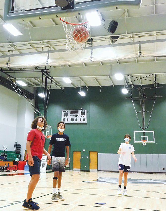 From left, Woods Charter freshmen basketball players Eli Hutter-DeMarco, Alex Smollen and Ethan Green participate in a free throw drill last Thursday on campus.