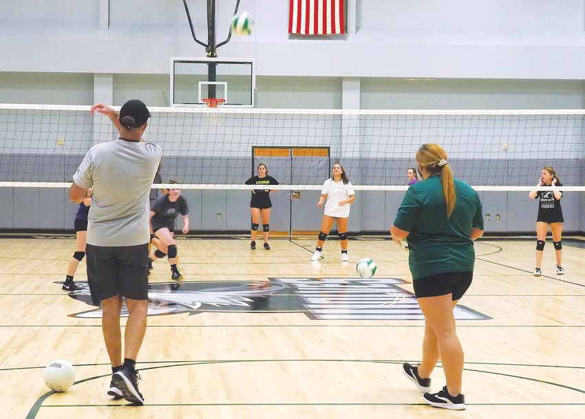 Woods Charter volleyball coach Scott Green (left) and assistant coach Taylor Ritchie toss balls into play and over the net for a return drill during an October skill session.