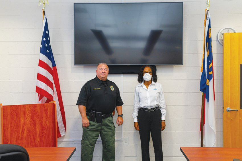 Siler City Police Chief Mike Wagner stands in his department's newly renovated emergency operations center that Duke Energy District Manager Indira Everett, right, helped to fund.