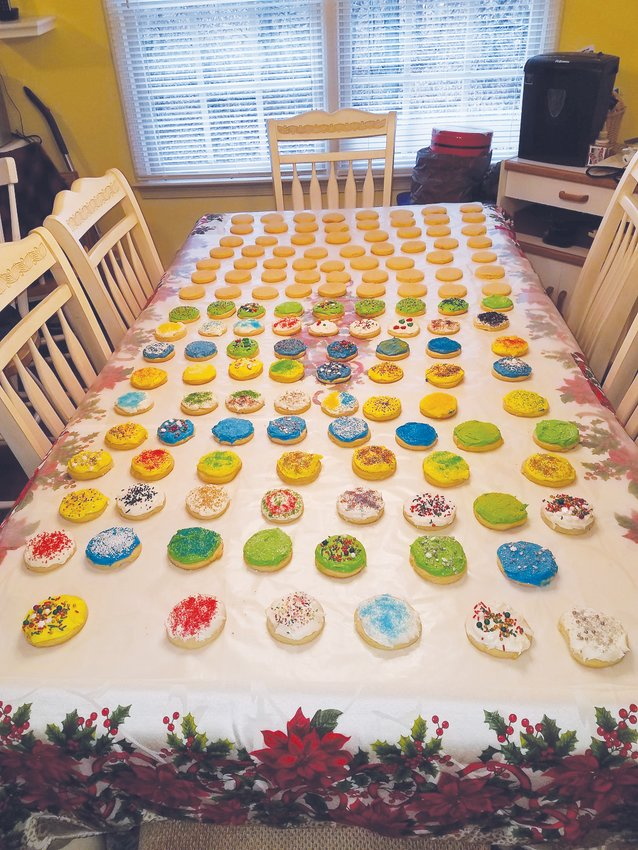 A table full of Christmas cookies — some decorated, some awaiting icing.