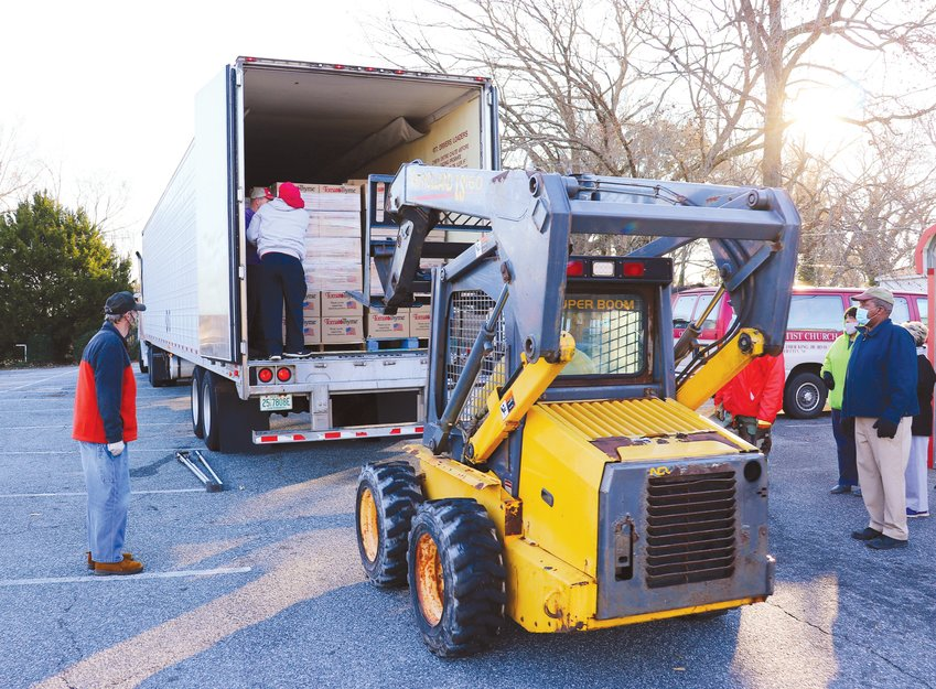 Volunteers unload the truck's 1,248 boxes in the parking lot of First Missionary Baptist Church on Dec. 18. Each box held $50 worth of food.