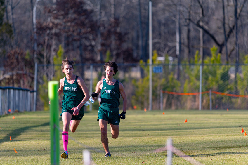 Research Triangle senior Josh Lewis (left) and Woods Charter senior Primo Costa (right) make a final sprint for the finish line at Wednesday's conferece meet. Lewis finished fourth; Costa finished fifth.
