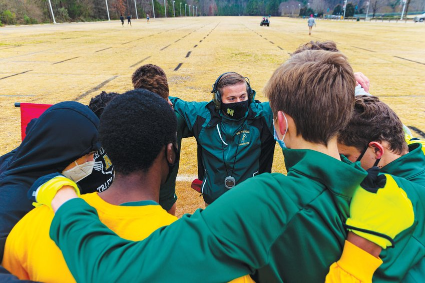 Northwood head coach Cameron Isenhour (center) huddles with his men's team ahead of the NCHSAA 3A mideast regional last Saturday.