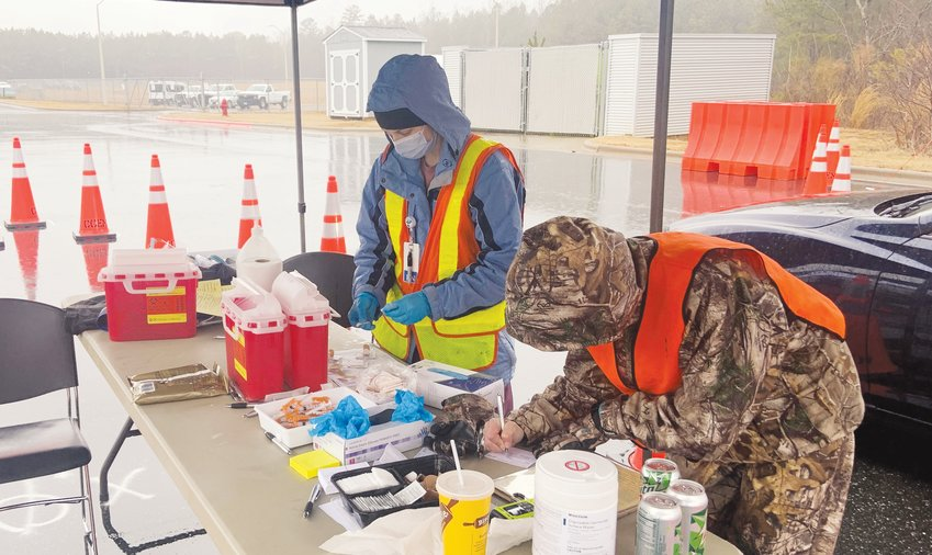 CCPHD Public Health Nurse Laura Parks, left, and Public Health Nurse Supervisor Bonnie Dukeman prepare a COVID-19 vaccine for administration Monday during a mass vaccination event at the Chatham County Agriculture & Conference Center in Pittsboro.