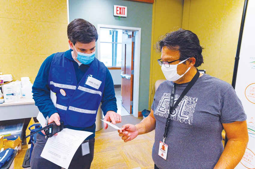 Chatham County Public Health Director Mike Zelek hands Alirio Estevez his second-dose appointment slip last Friday.