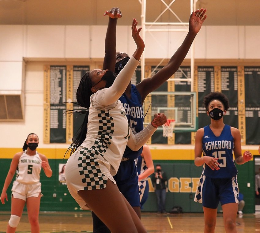 Northwood sophomore forward Te'Keyah Bland (12) waits to grab a rebound alongside Asheboro senior forward Diamond McDowell (5) in the Chargers' 54-44 loss to Asheboro on Tuesday in the East Regional title game. Bland (13 points) and McDowell (22 points) battled in the paint all night long.