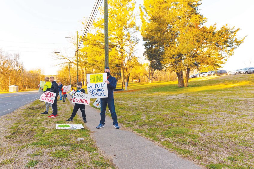 A small gathering of parents and students gathered outside of Horton Middle School prior to the CCS Board of Education's meeting on Monday, urging the board to move to Plan A. Pictured here are the few people who remained shortly before the meeting began, while others checked in to speak during the public comments session.