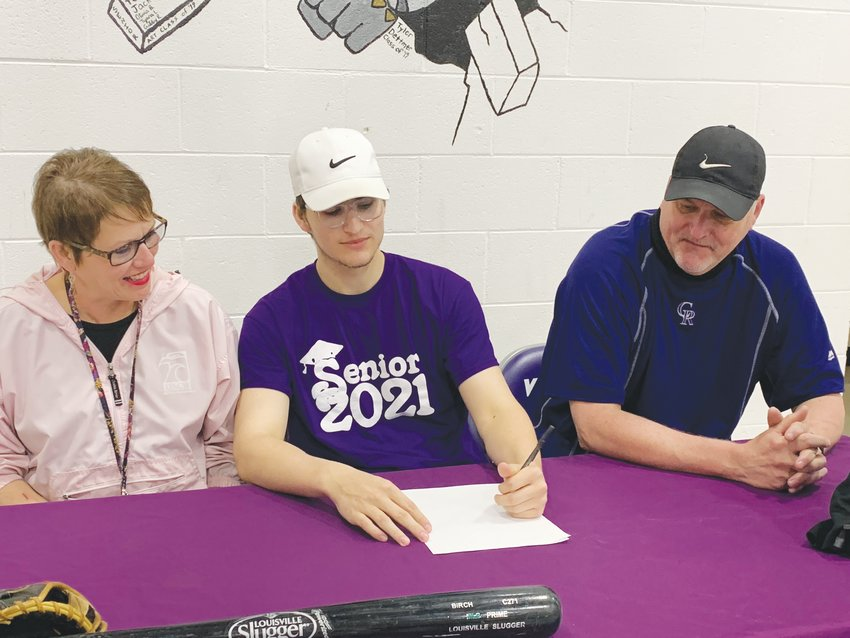 Trevor (center) signs a letter of intent with Brunswick Community College on March 9 as his parents, Kelly (left) and Richard Golden look on.