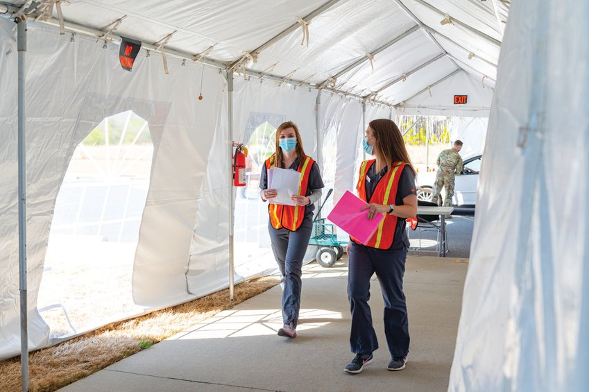 Julia Pitts (left) and Brianna Reeves, nursing students at UNC, act as runners for documents and materials from point to point — a critical component of the Chatham Ag Center's vaccine distribution operation.