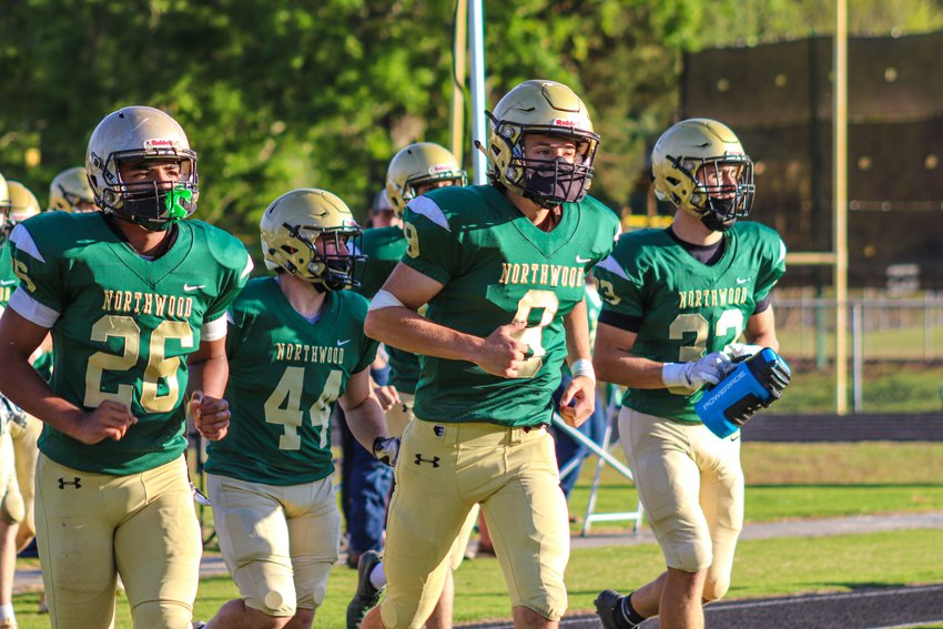Led by senior quarterback Cam Entrekin (9), the Northwood Chargers run out onto the field ahead of their first-round playoff matchup with the West Carteret Patriots on Friday, April 16. Northwood won 17-0, scoring all of their points in the first half.
