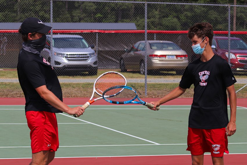 Chatham Central senior duo Jayden Gilliland (left) and Preston Cox tap rackets after a point during their doubles finals match against a North Stanly duo in the Yadkin Valley Conference tournament on Thursday. Gilliland and Cox won the tournament without dropping a game.