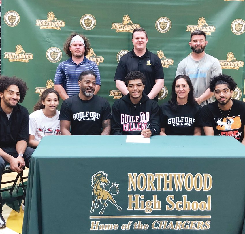 Northwood senior runningback/linebacker Hue Jacobs (center, with pen) signs his letter of intent to play football at Guilford College next season at a signing day event alongside his family, coaches and Northwood staff last Thursday.