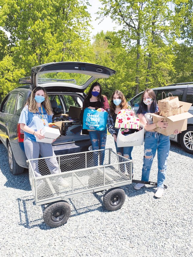 Geneva Yarger-Woolford (left), Annika Lowe (right), Angelina Parker-Lewis (second from right), and Emma Dickerson drop off donated hygiene and period products at the West Chatham Food Pantry on April 23. Their donation drive collected over $14,000 worth of donations.