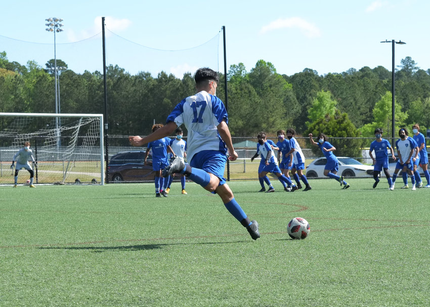 Siler City FC's Diego Valdez Plata (17), a member of the U17 boys' team, attempts a spot kick in his team's 3-1 victory over Wake FC to take the Tournament of Champions crown on April 25.