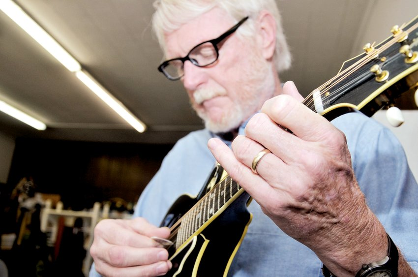 In this 2019 file photo, Tommy Edwards lays down a couple of riffs on the mandolin at his antiques, arts and music shop in Pittsboro. Edwards died Saturday at the age of 75 after a battle with pancreatic cancer.