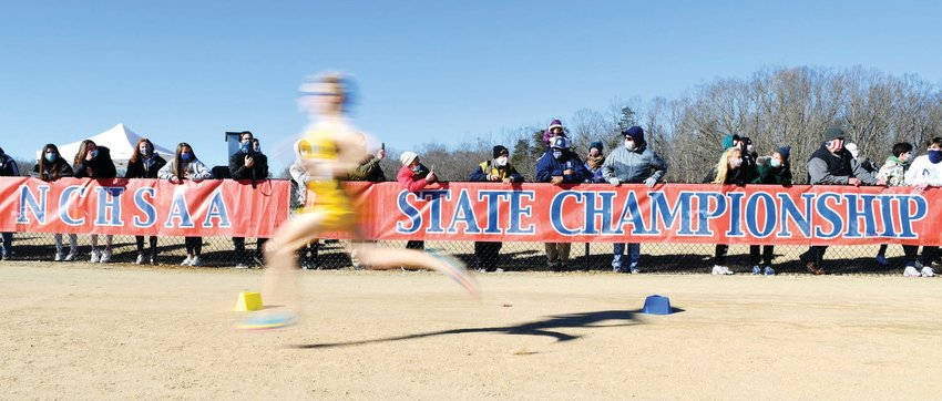 Bundled in warm clothes, spectators look on as runners approach the finish line at the NCHSAA state cross country meet in January. The two-day championship event, typically held in early November, is one of 17-plus state championship events put on by the NCHSAA each year.