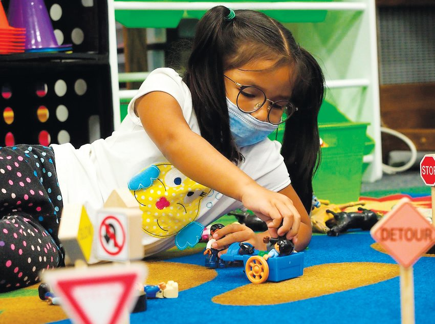 Andrea, a 4-year-old Pre-K student, creates a town with signs, animals and people at Bennett School on Monday morning.