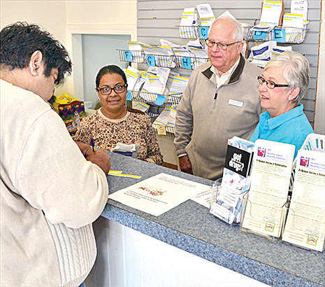 Pharmacy manager Lynn Glasser, second from the right, and staff help a customer.