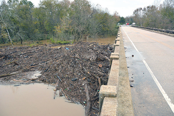 Downed trees and debris piled up against bridges along the Deep River including this one at Plank Road.