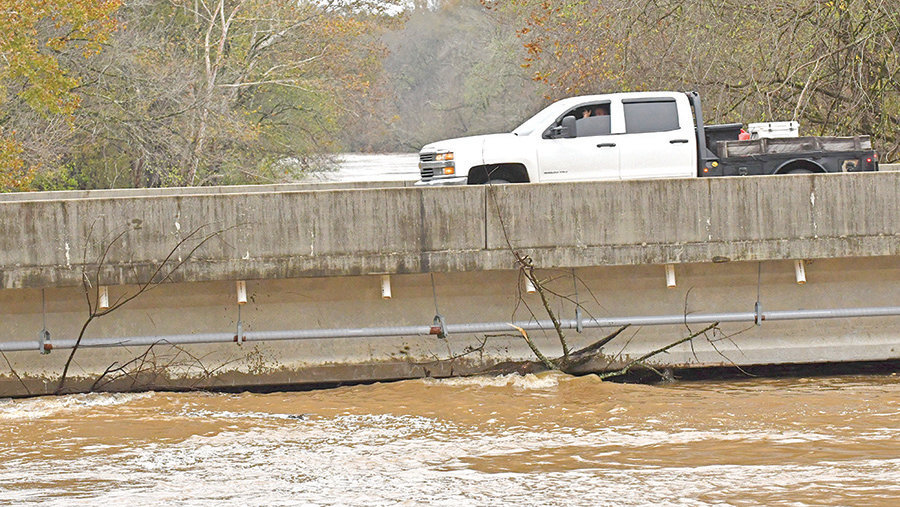 A motorist crosses the bridge at the Deep River in Cumnock. More heavy rains last week caused additional flooding in Chatham County, closing some roads and raising river levels on some bridges to just below the bridge level.
