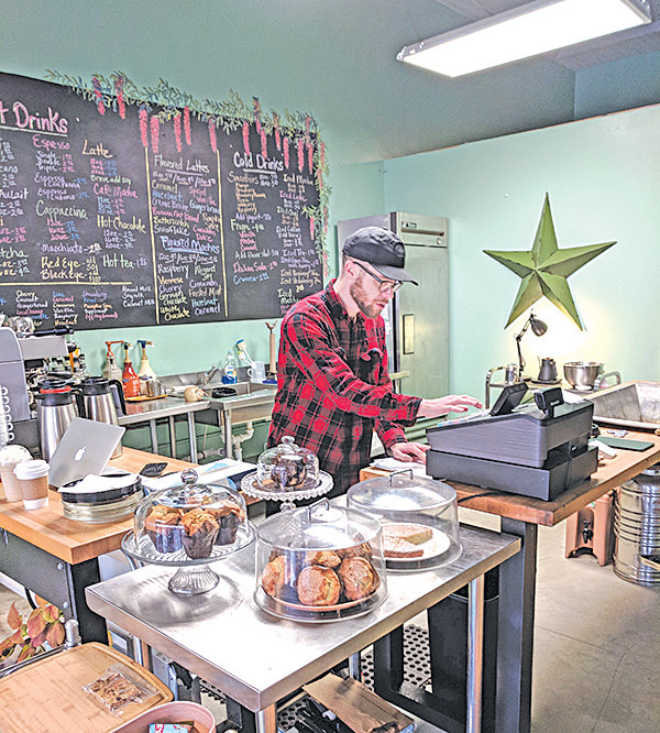 Jake Brower, a local artist and barista at Courtyard Coffee at Peppercorn in Siler City serves up customers during Small Business Saturday.
