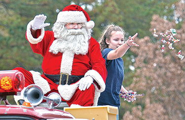 Santa waves as candy is thrown out in Goldston
