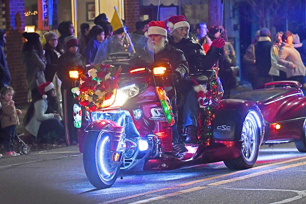 One of Santa's helpers rides through the street on a motorcycle.
