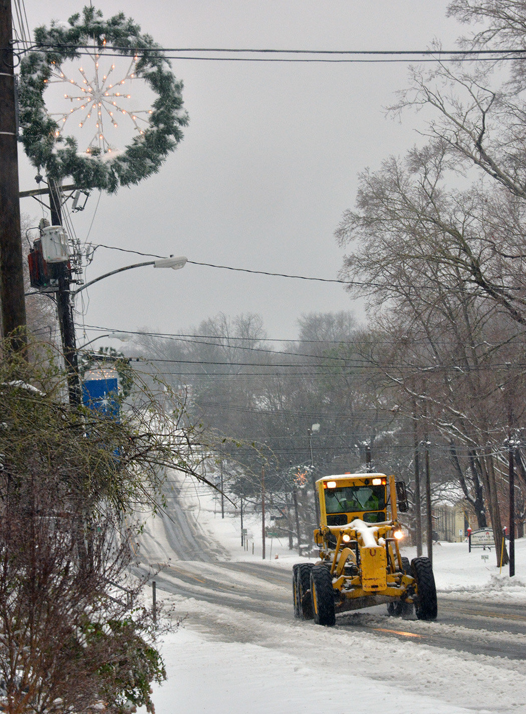 In Pittsboro, the Christmas decorations lit the way for a motor grader to clear another Chatham road.