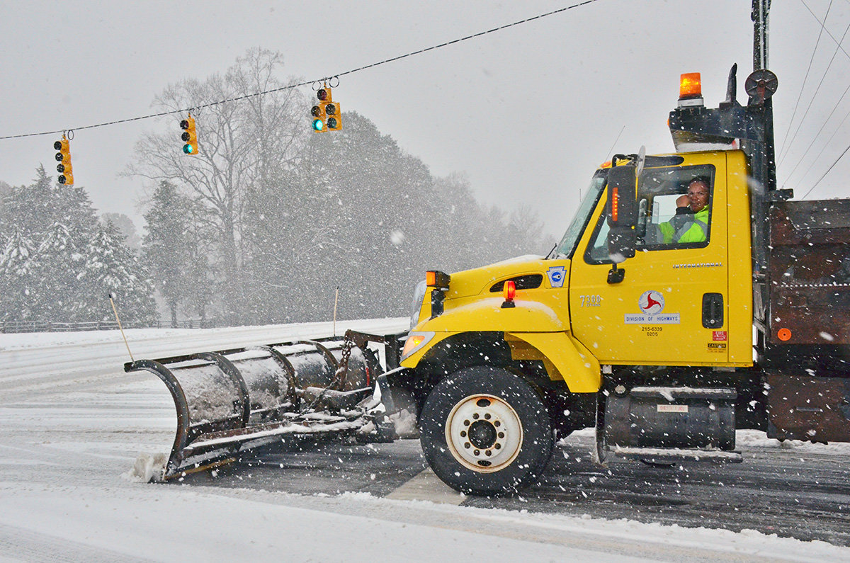 Snow falls as a DOT truck scrapes an intersection on Highway 64 in Siler City
