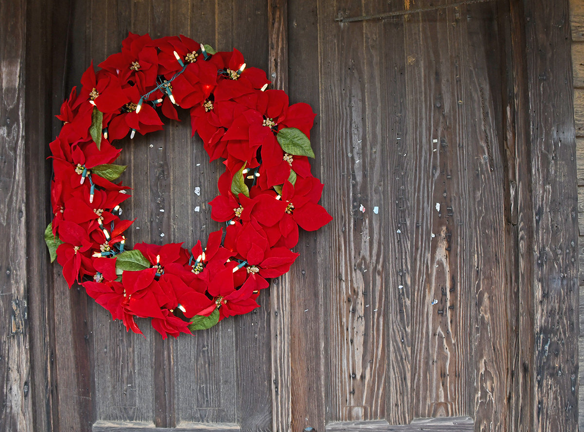A bright red Christmas wreath hangs on the old wooden front door at Sharpe's Store.