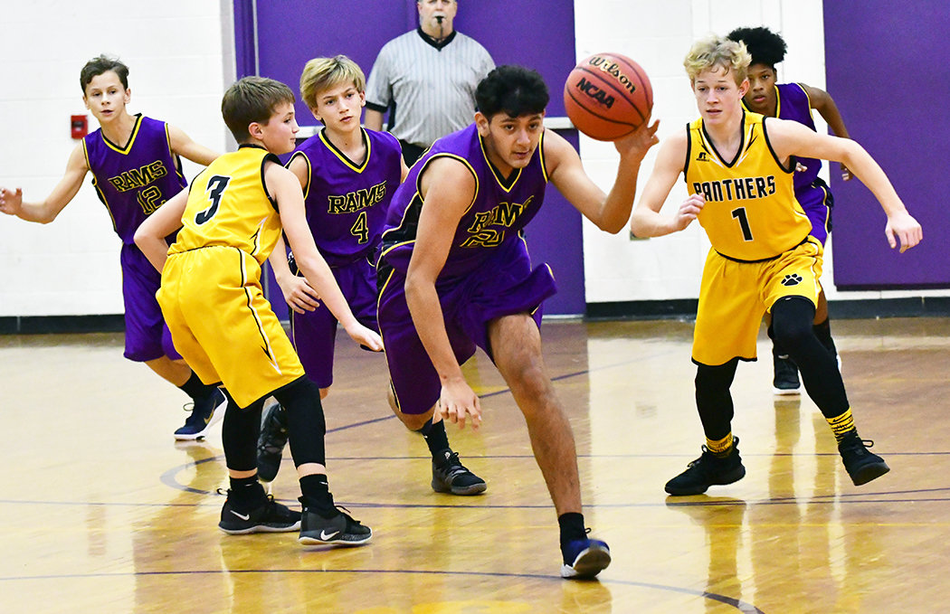 Chatham Middle's Juan Soto, center, moves the ball upcourt between Bennett's Jacob Gilliland, 3 and Matthews Smith, 1.