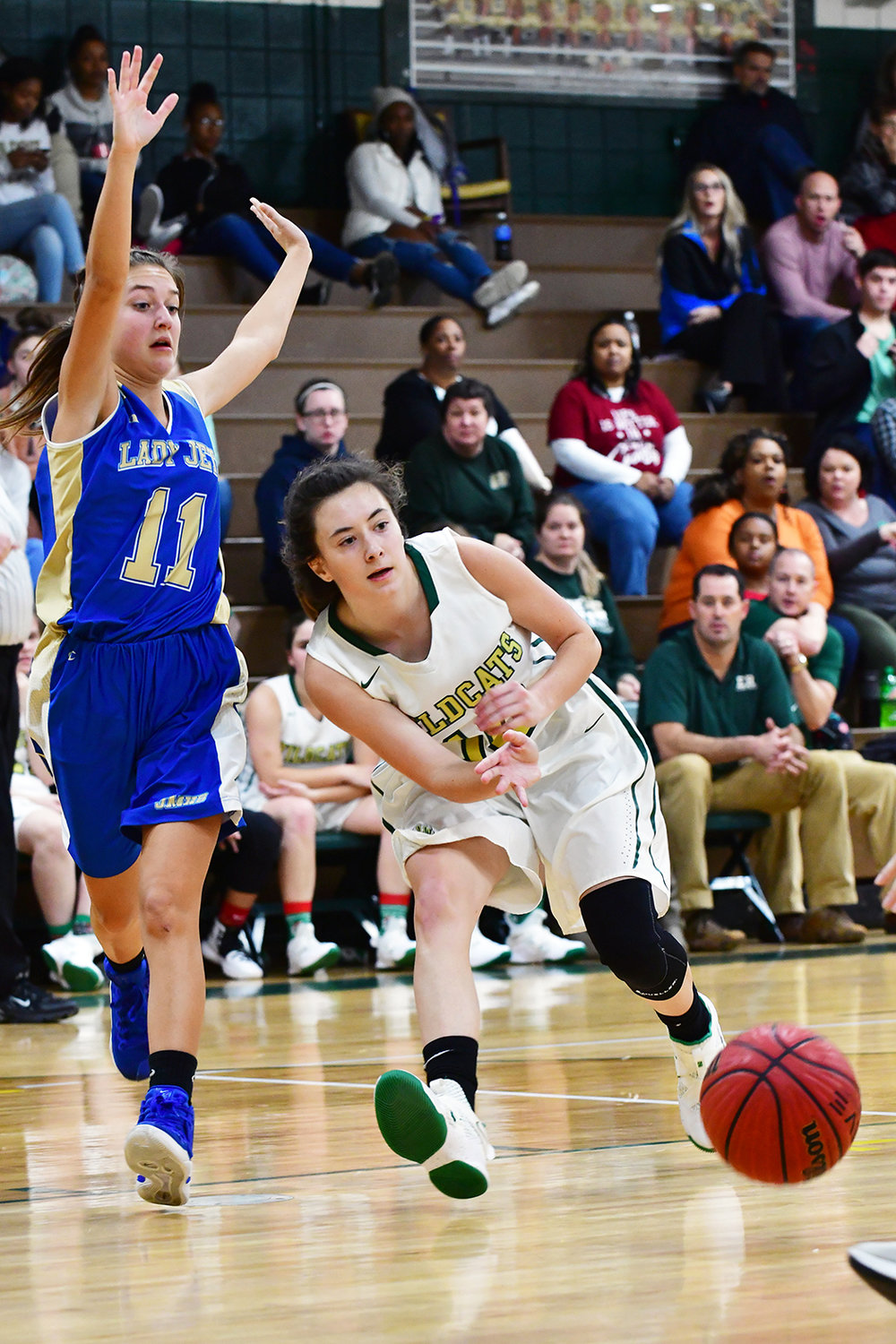 Lady Wildcat Lilly Whitaker passes the ball as Jet Avery Headen applies defense. The Lady Jets lost their game 47-44.