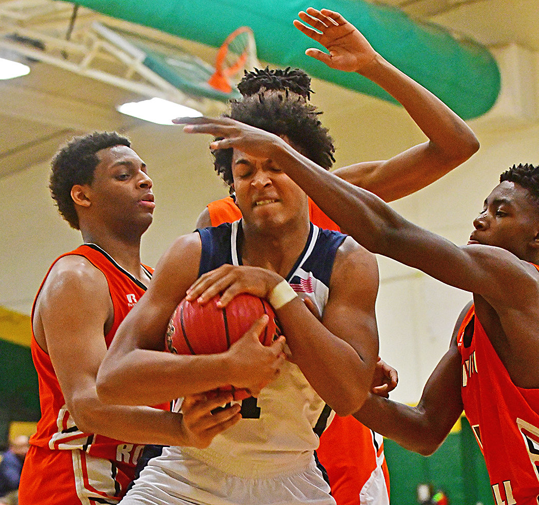 Apex Friendship Patriot Kenny Noland, center, cover s the ball up against Wallace-Rose Hill in first round action. Apex won the game 62-43.