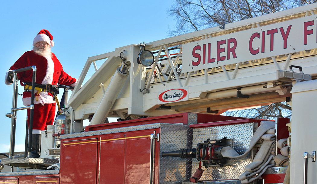 Santa Claus rides on the back of the ladder truck Saturday in a residential area off of Hampstone Road in Siler City.