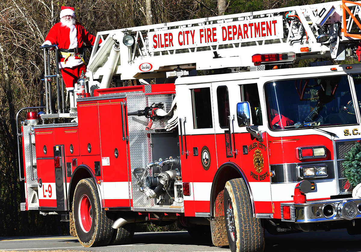 Santa is driven through a neighborhood Saturday, greeting kids, and adults in anticipation of Christmas Eve Monday.