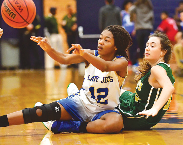Lady Jet Seniah Wiley passes the ball from the floor after capturing control of a loose ball while Eastern Randolph's Lilly Whitaker looks on in the Courier-Tribune Invitational. JM went on to the win over Eastern Randolph but lost their game to Wheatmore on Saturday.