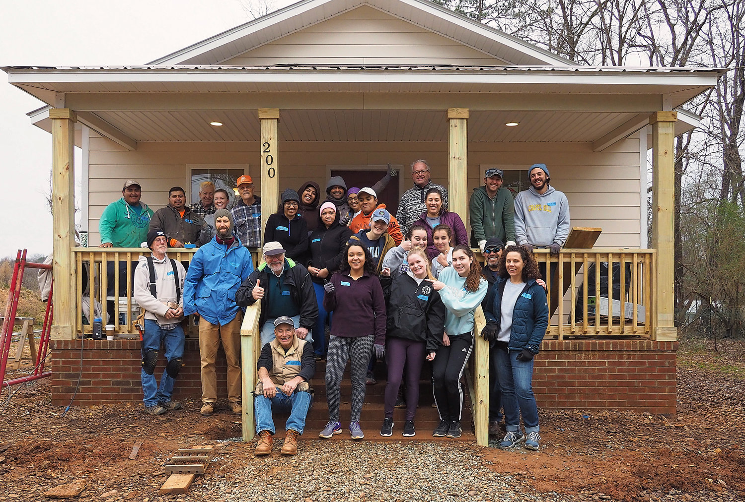 Staff and volunteers stand on the porch the home they worked on during the day of service event on Saturday. They are joined by Dania Gonzales, (center in the purple top), who will own the home after the build is complete.