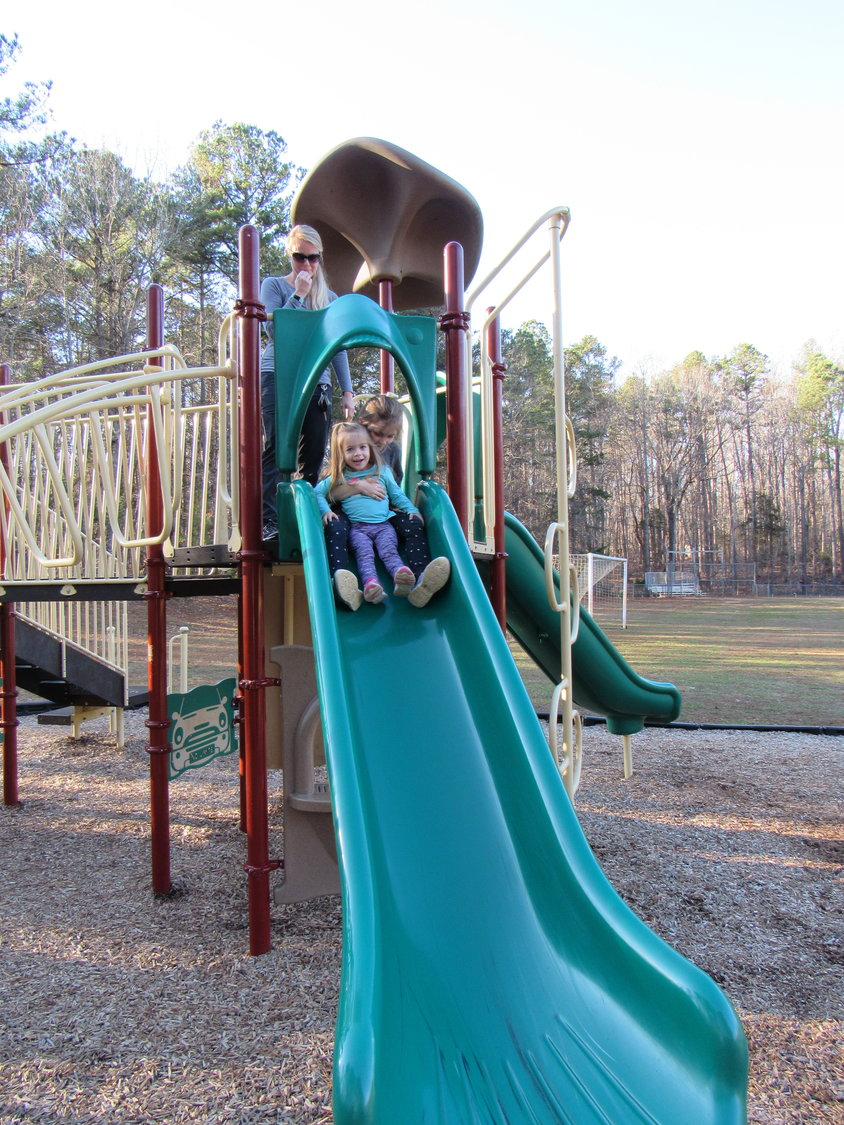 Grace Lux, 2, of Pittsboro smiles at the camera before she and her sister Haley, 7, go down the slide at Northwest District Park in Siler City. Mother Ashley looks on.