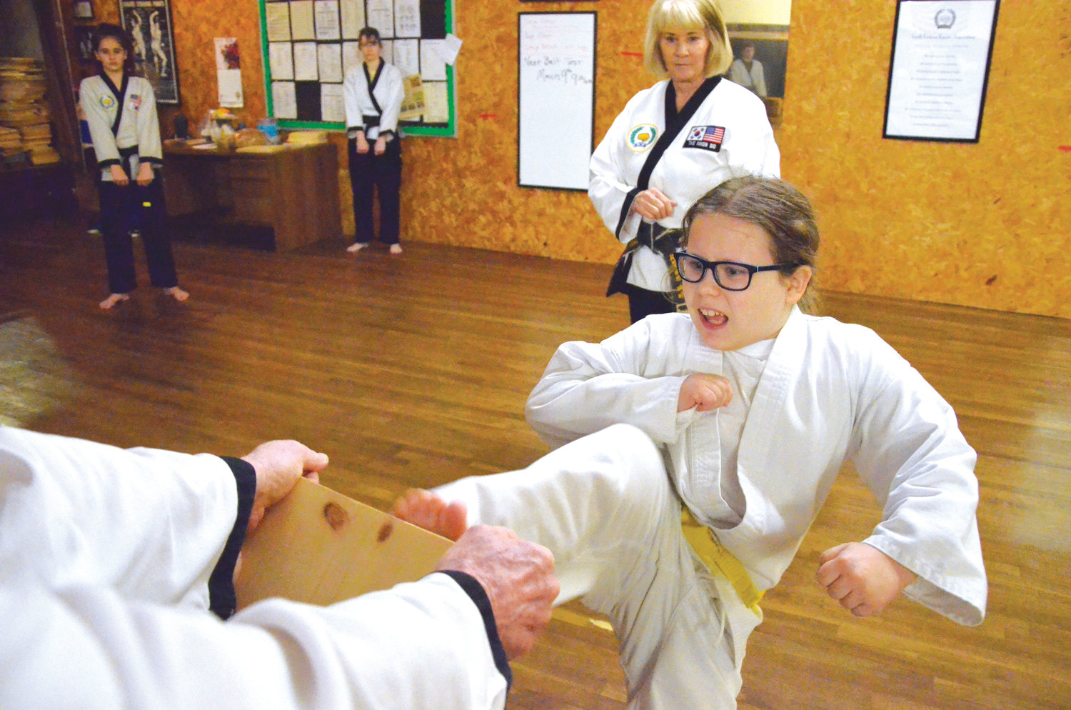 She's only 9 years old, but student Clara Hallberg is breaking half-inch thick boards just like the adults. After careful instruction by Master Peggy Jolly, shown watching, yellow-belt Hallberg kicked the board in two.