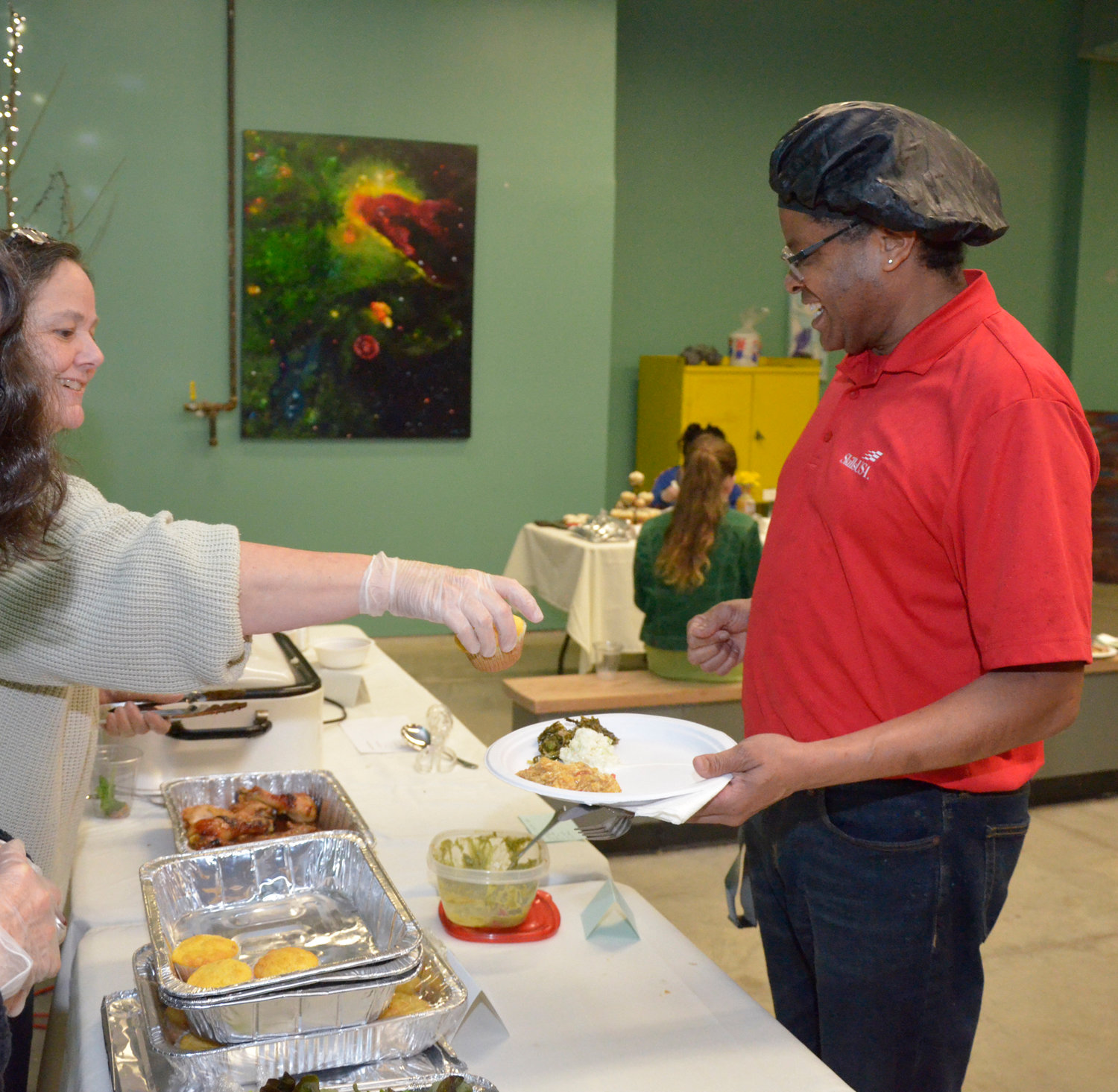 Tamsey Hill gives cornbread to Everett Goldston Jr., the Family and Consumer Sciences teacher at Chatham Central High School.  Some of his students prepared and served the meal for the evening.