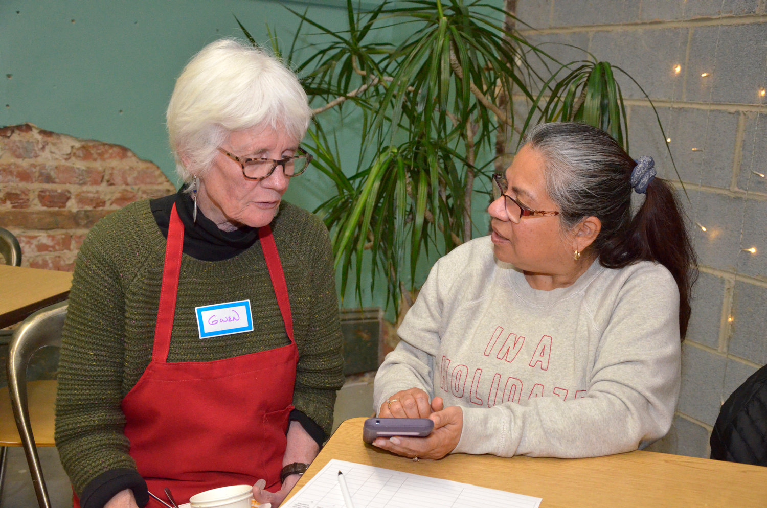 Gwen Overturf, left, talks with Maria Soto at the free supper event.  Soto said that she comes to meet new people, and interact with others.