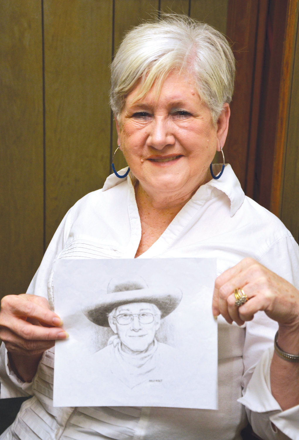 Linda Lehman holds a drawing of her late uncle, Milo Holt, who did much during his lifetime to celebrate and promote B-Western movies. Lehman is busy planning the 8th Annual Milo Holt Western Festival, returning to downtown Siler City in May.