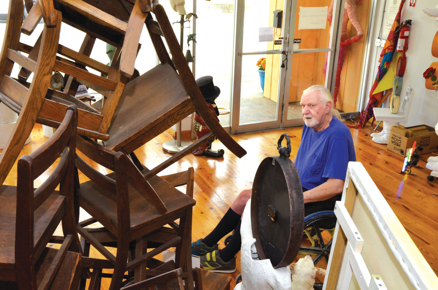 Roger Person sits beside a wooden chair sculpture in his studio on North Chatham Street in Siler City. These school chairs once were used as generations of students went through school in Siler City. Now they are used to teach creativity and art.