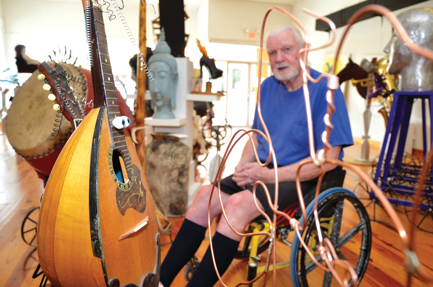 He's an unconventional artist, using found objects and pieces to fit into his art. Here, an old mandolin plays a new tune as a piece of art in Roger Person's studio.
