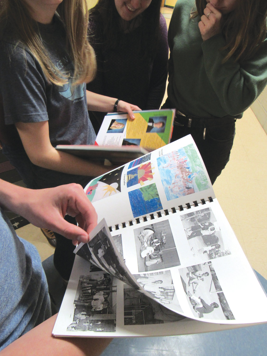 Members of Woods Charter's yearbook staff compare the 2003-2004 edition, foreground, and last year's yearbook.