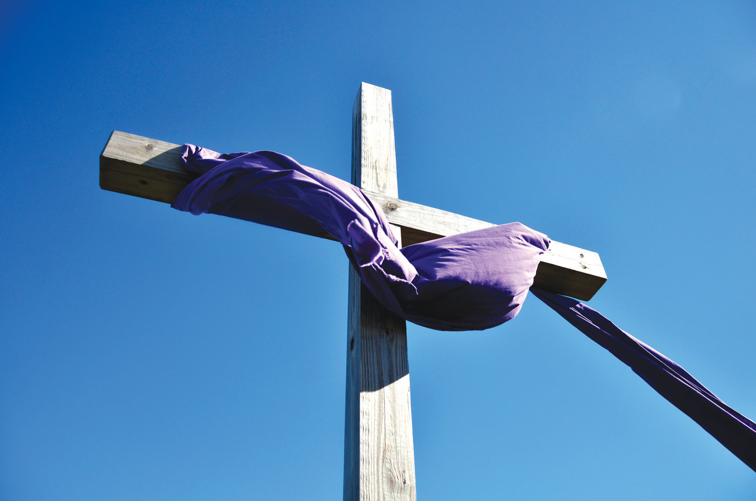 The center cross of the three crosses has a purple cloth attached to show the royalty of Jesus. It represents the day that Jesus rode into Jerusalem on a donkey as a King.