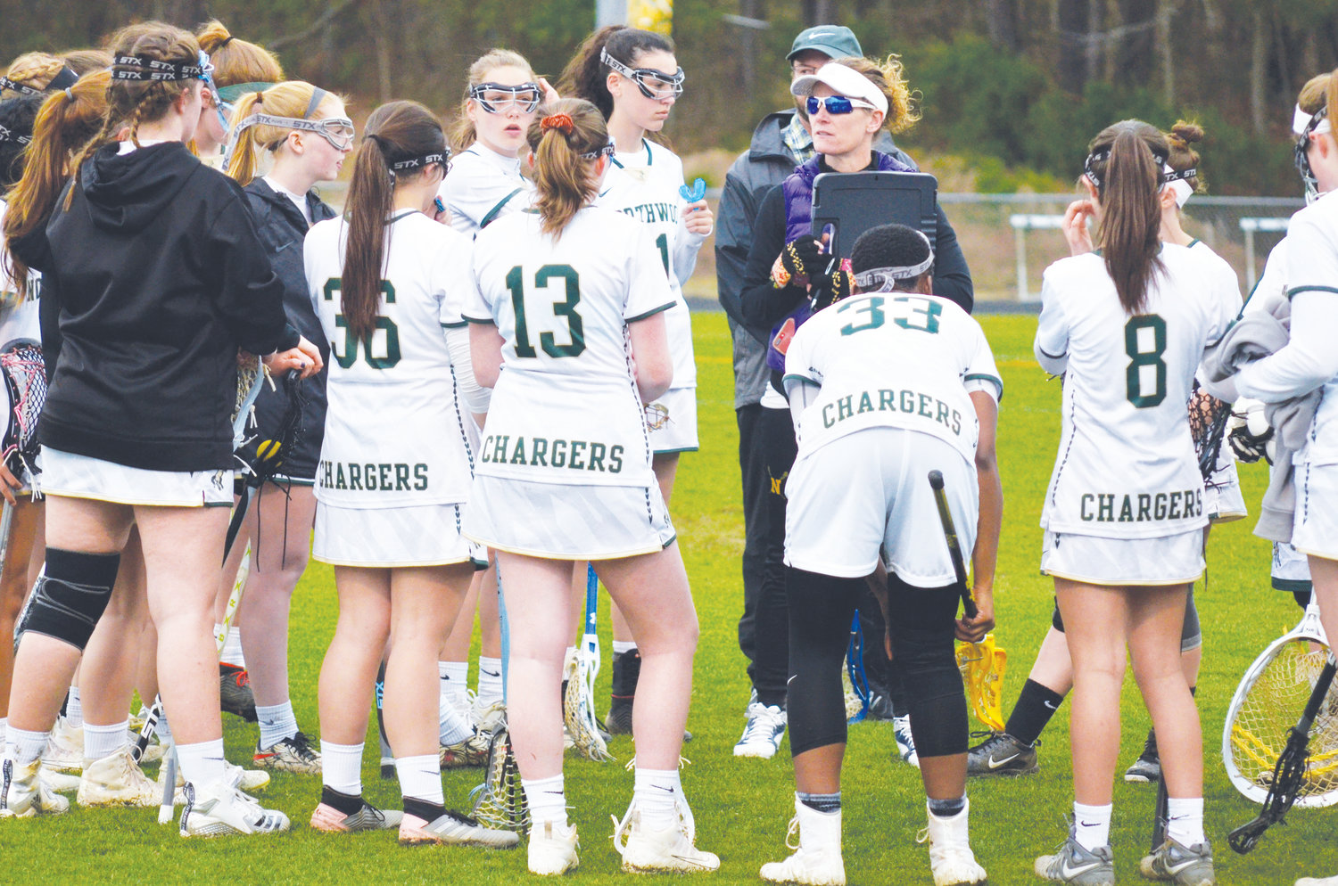 Coach Amanda Huegerich instructs her girls on the Northwood Girls Lacrosse team just before starting their game in recent high school action.