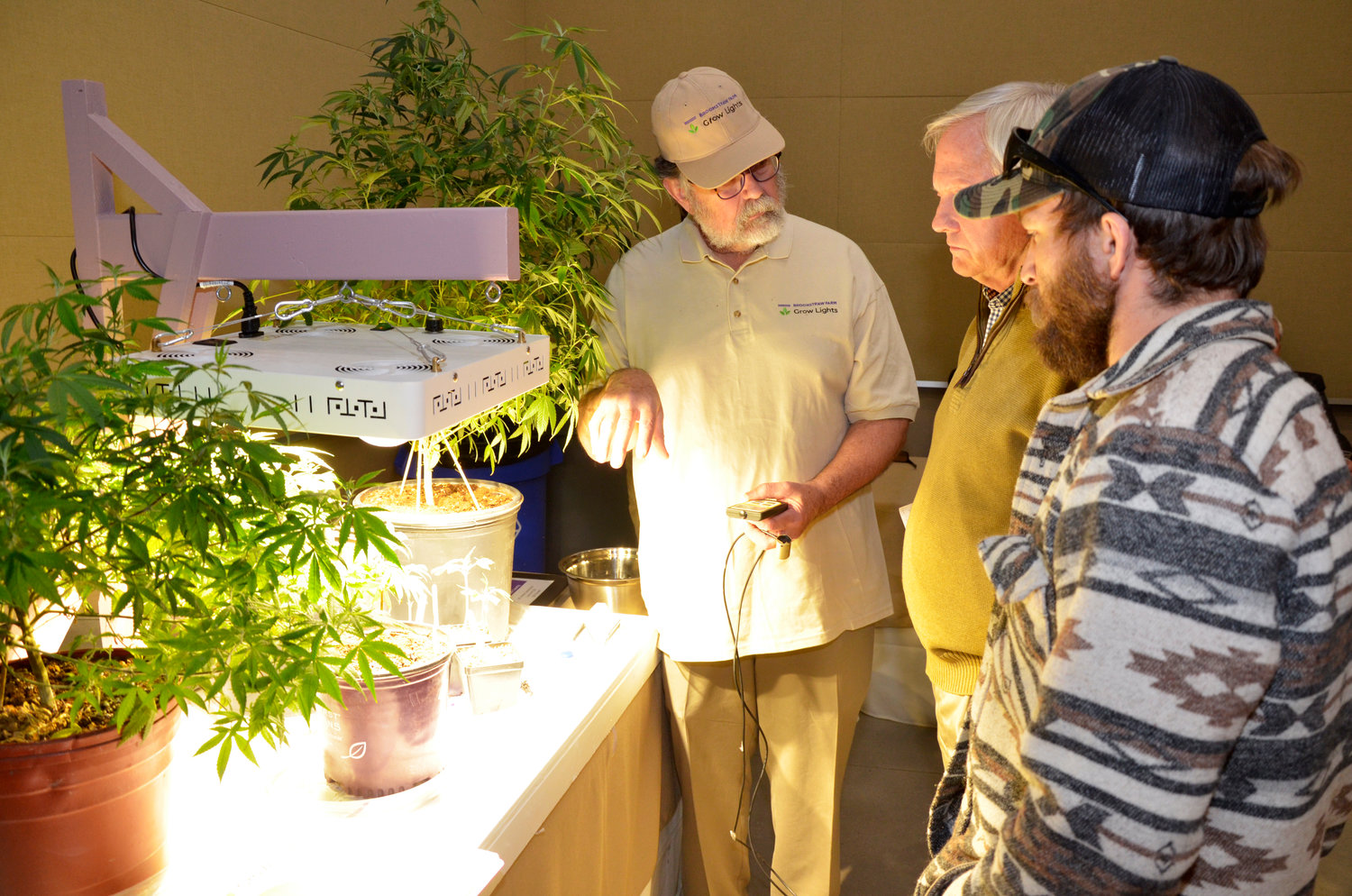 In the exhibition hall at the Agricultural Center in Pittsboro, … of Brookwood Farms talks with … and …. about the lumen sensor device and the growth lights hanging above the cannabis plants.  The device shows the user the amount of light needed by the plants in order to maximize their growth.