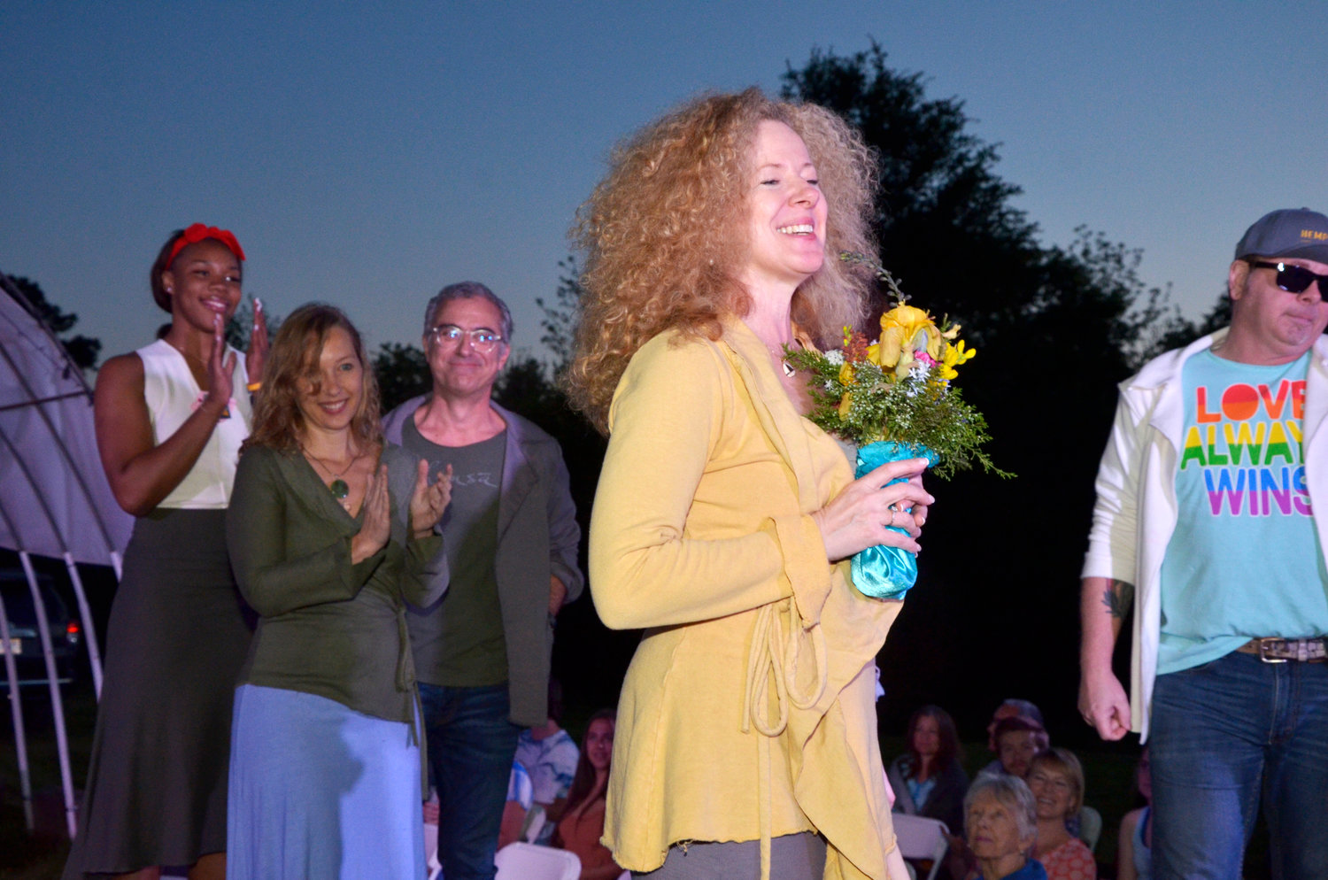 After showing her collection at the East Coast Runway event in Pittsboro Saturday, one of the four designers gets flowers and applause for her work.