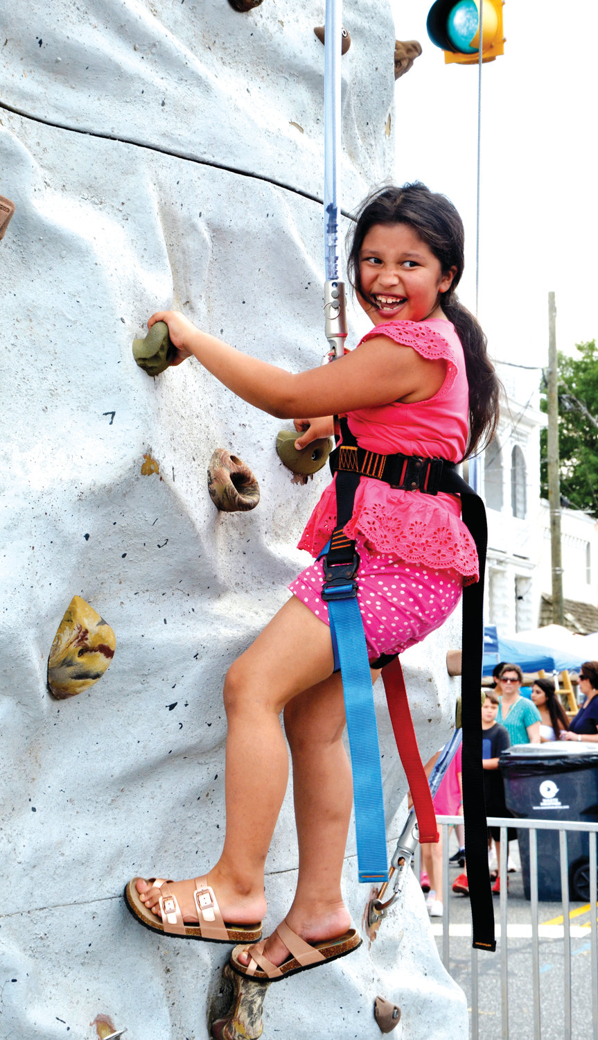Ruth Interiano, 10, takes a climb on the rock wall set up on Chatham Avenue at Saturday's Spring Chicken Festival.